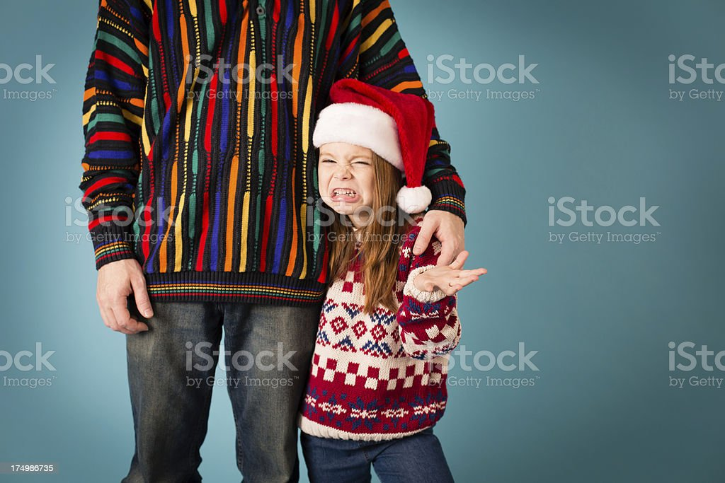Little Girl Making Face at Dad, Both Wearing Ugly Sweaters stock photo
