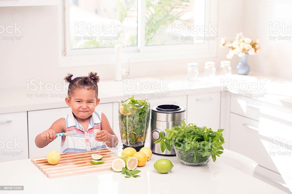 Little girl making face. Sour taste of lemon. stock photo