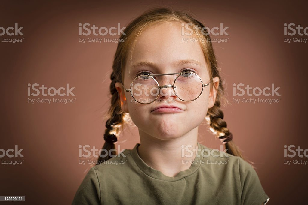 Little Girl Making Face While Wearing Vintage Nerdy Glasses royalty-free stock photo