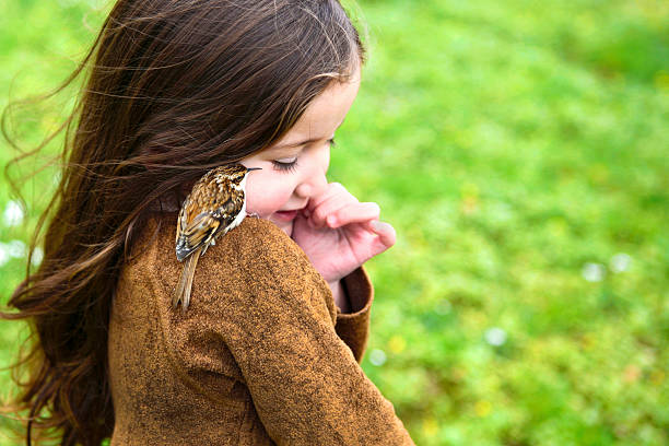 Little girl making friend with a bird stock photo