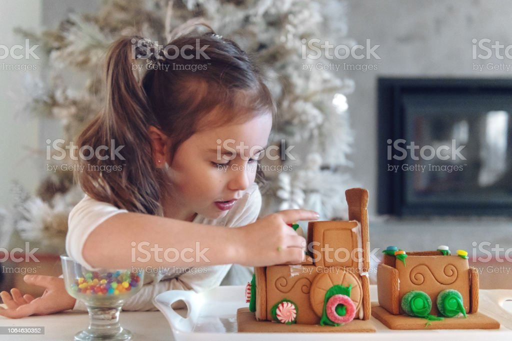 Little girl making gingerbread train stock photo