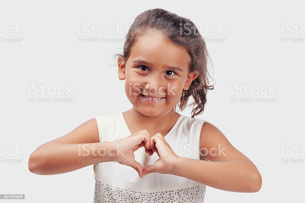 Little girl making heart shape with hands stock photo