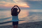 Girl at the beach showing heart shape symbol at sunset