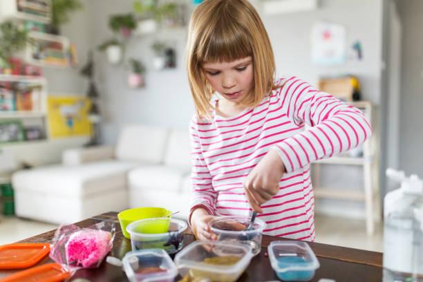 Kleines Mädchen, das hausgemachtes Schleimspielzeug herstellt – Foto