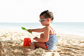 Side View Of A Little Girl Building Sand Castle With Plastic Bucket On Beach