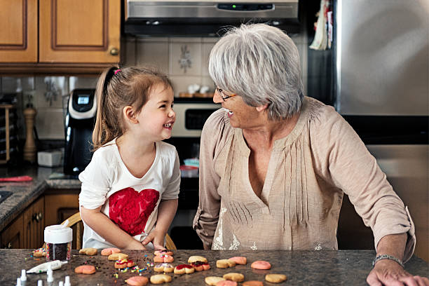 little girl making valentine's cookie with grandma - senior valentine stock photos and pictures
