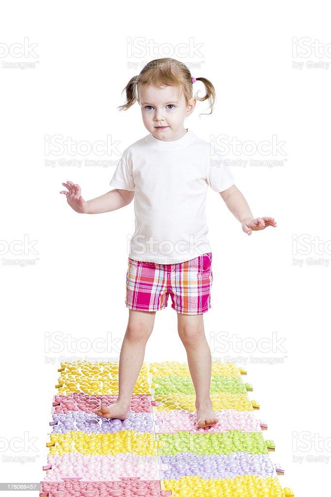 little girl massaging her feet on mat stock photo