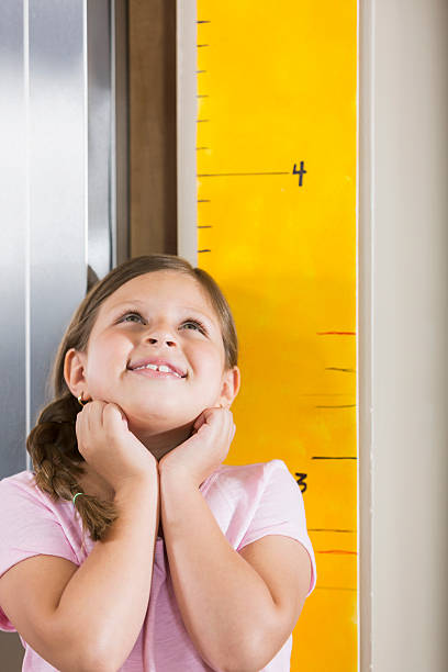 Little Girl Measuring Her Height On Growth Chart Stock Photo More
