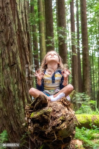 Little girl looking up meditating at the woods