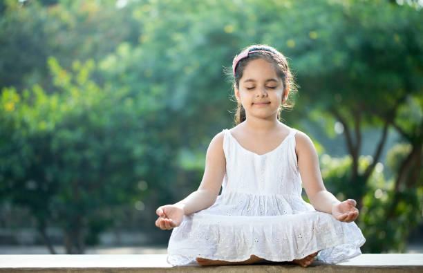 Little girl meditating outdoors at park stock photo