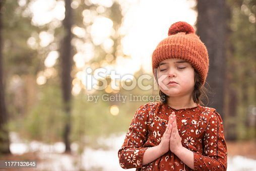 An adorable little girl stands outside on a cold winter day. She is meditating outside in nature. She is at peace. She is wearing a hat.