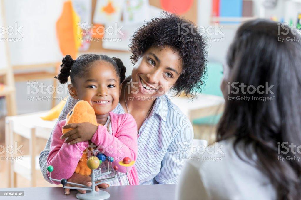 Little girl meets new preschool teacher with mom stock photo