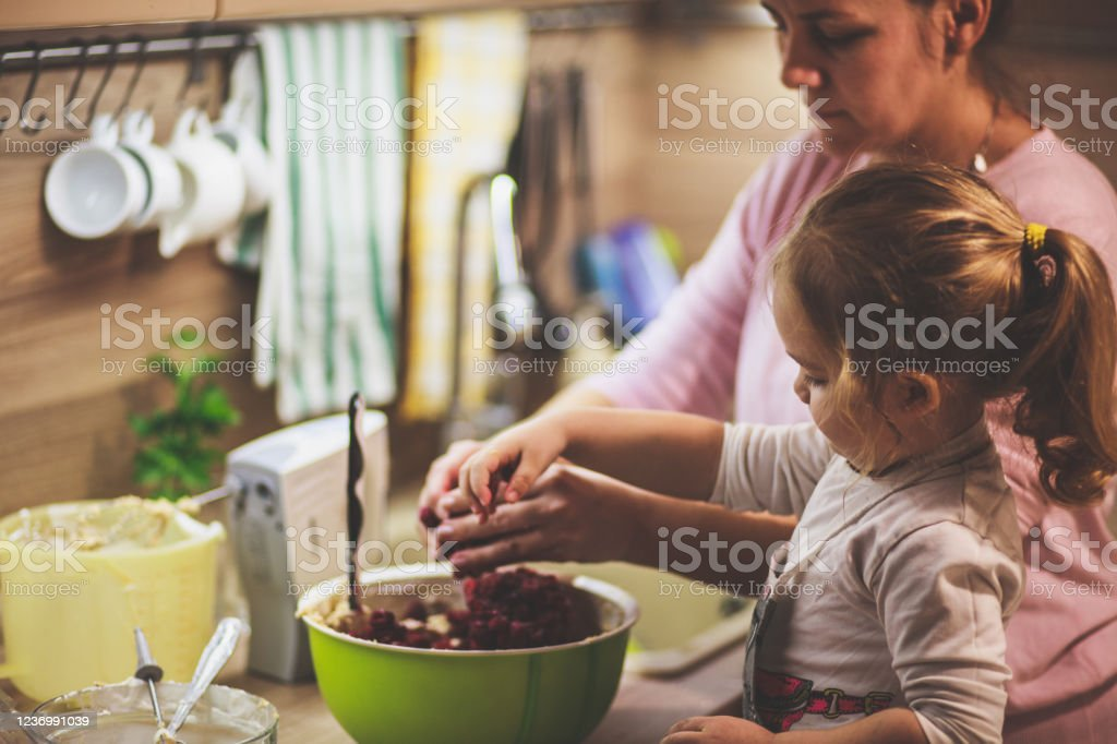 Little girl mixing cherries in the cake batter with her mother Copy space shot of cute three year old girl assisting her mother in mixing in the cherries in with the cheesecake batter they are preparing together. 2-3 Years Stock Photo