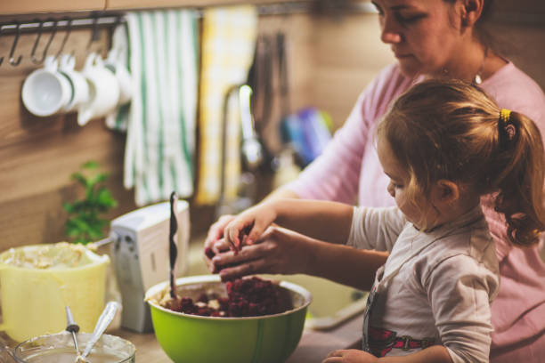 little girl mixing cherries in the cake batter with her mother - all vocabulary foto e immagini stock