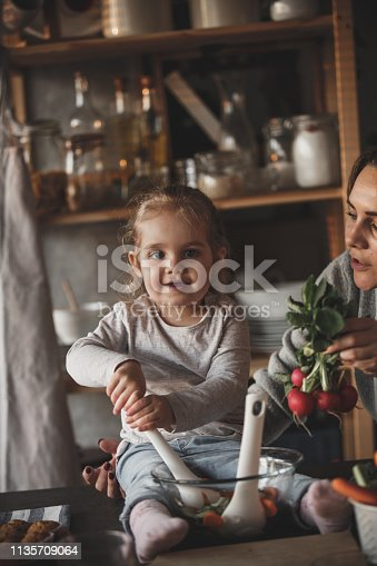 istock Little girl mixing vegetables, preparing salad 1135709064