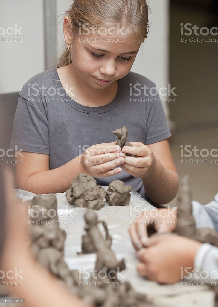 Little girl molding clay at a table stock photo