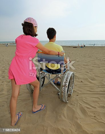 little girl pushes the wheelchair on the sandy beach with a young boy in summer