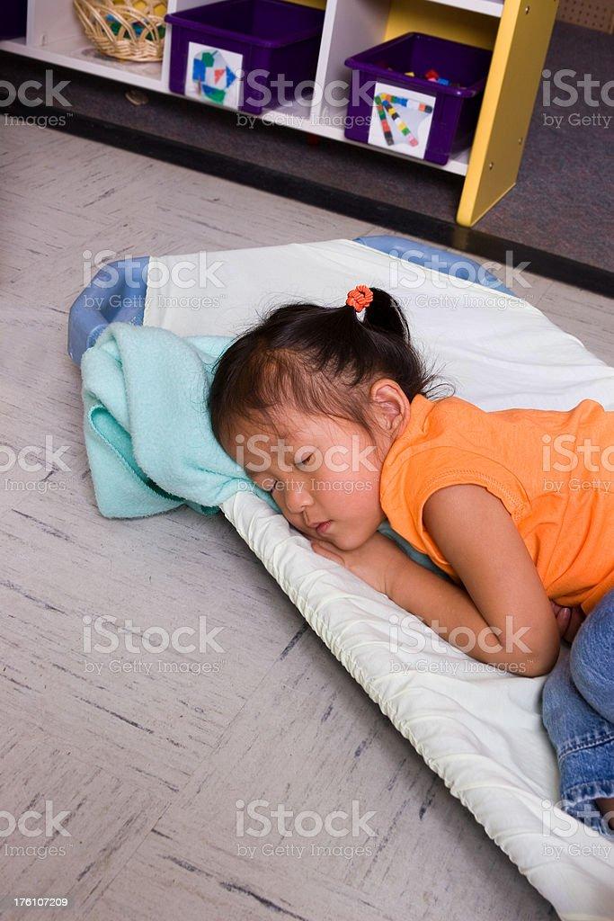 Little girl naps on cot at preschool stock photo