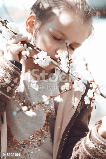 istock A little girl near a flowering apricot tree. 948502194