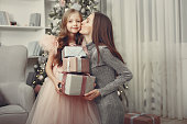 Cute little girl in a pink dress. Child standing by the christmas tree