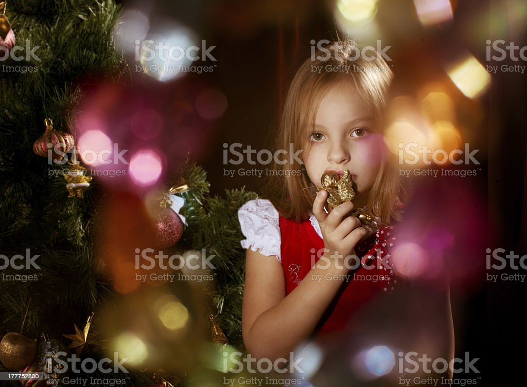 Little girl near Christmas tree with magic irradiance stock photo