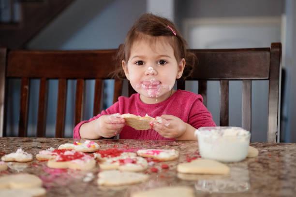 kleines mädchen von ca. 2-3 jahre alt geschmack cookies herzform während valentinstag - 3 zutaten kuchen stock-fotos und bilder