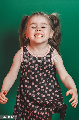 1035967418 istock photo Little girl of three years with tails in dress posing in studio on green background 1224856074