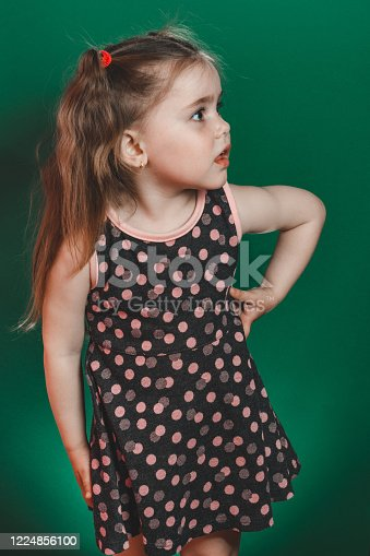 1035967418 istock photo Little girl of three years with tails in dress posing in studio on green background 1224856100