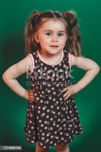 1035967418 istock photo Little girl of three years with tails in dress posing in studio on green background 1224856164