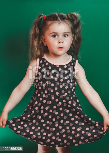 1035967418 istock photo Little girl of three years with tails in dress posing in studio on green background 1224856208