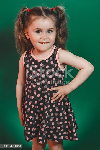 1035967418 istock photo Little girl of three years with tails in dress posing in studio on green background 1227092320