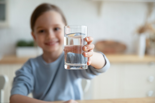 Close up of happy little Caucasian girl offer crystal still mineral water for body refreshment, smiling small European child recommend daily dose of clean aqua, dehydration, healthy lifestyle concept