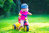Children riding a bike. Kids enjoying a bicycle ride. Little preschooler girl having fun outdoors. Active toddlers play in the garden. Summer fun in a park. Child wearing safety helmet.