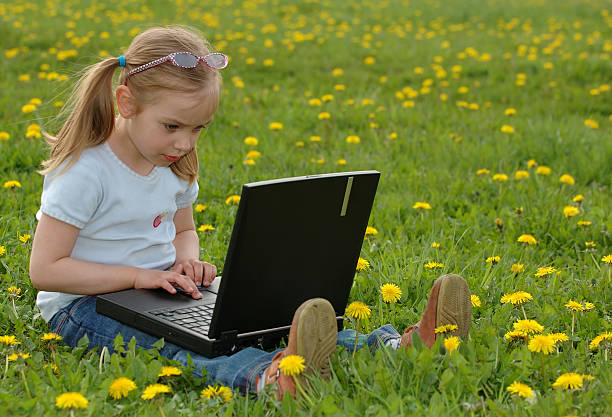 Little girl on a meadow with laptop stock photo