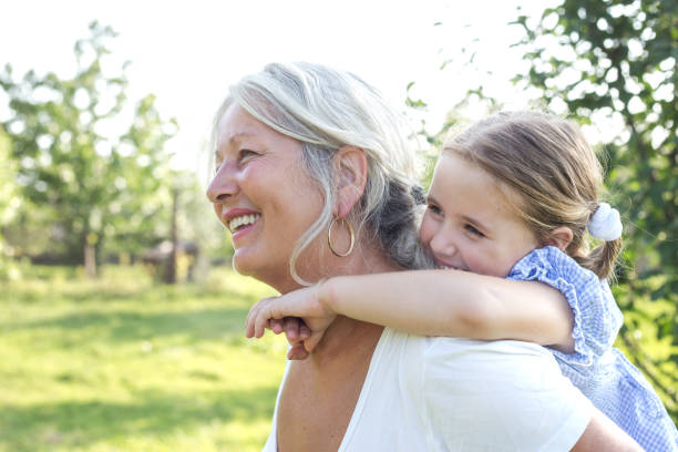 Little girl on a piggy back ride with her grandmother Grandmother and granddaughter playing outdoors. grandmother stock pictures, royalty-free photos & images