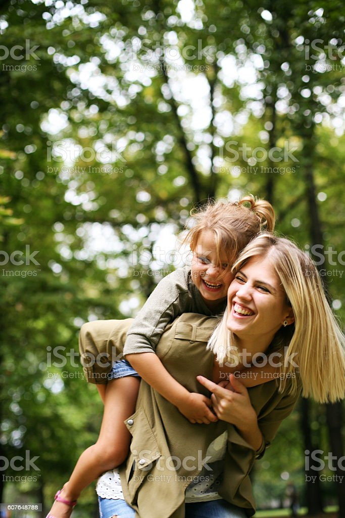 Little girl on a piggy back ride with her mother. royalty-free stock photo