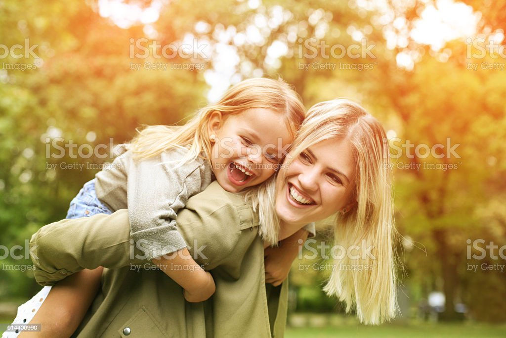 Little girl on a piggy back ride with her mother. foto stock royalty-free