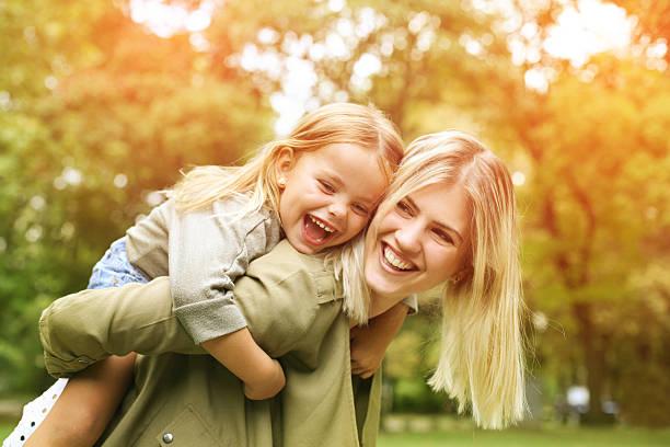 little girl on a piggy back ride with her mother. - sarı saç stok fotoğraflar ve resimler