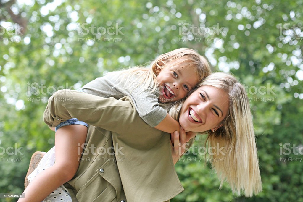 Little girl on a piggy back ride with her mother. stock photo