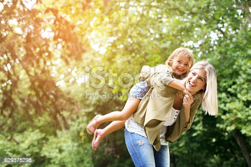 istock Little girl on a piggy back ride with her mother. 629375298