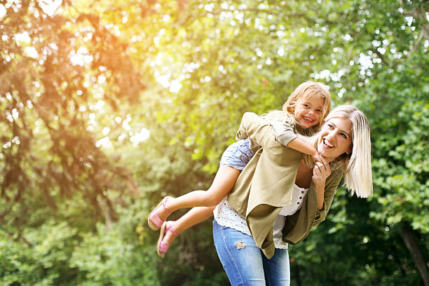 Little girl on a piggy back ride with her mother. Cute young daughter on a piggy back ride with her mother. Looking at camera. piggyback stock pictures, royalty-free photos & images