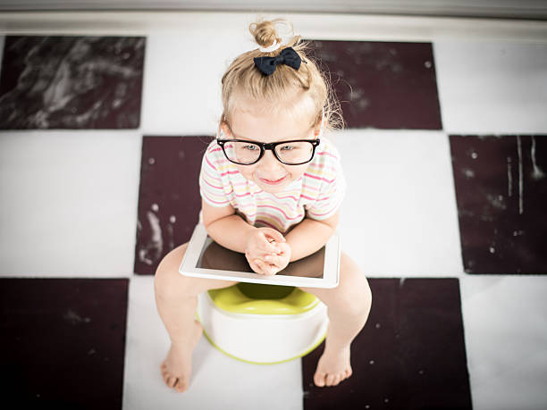 Little girl on a potty with tablet PC stock photo