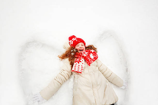 Little girl on a snow showing angel figures. – Foto
