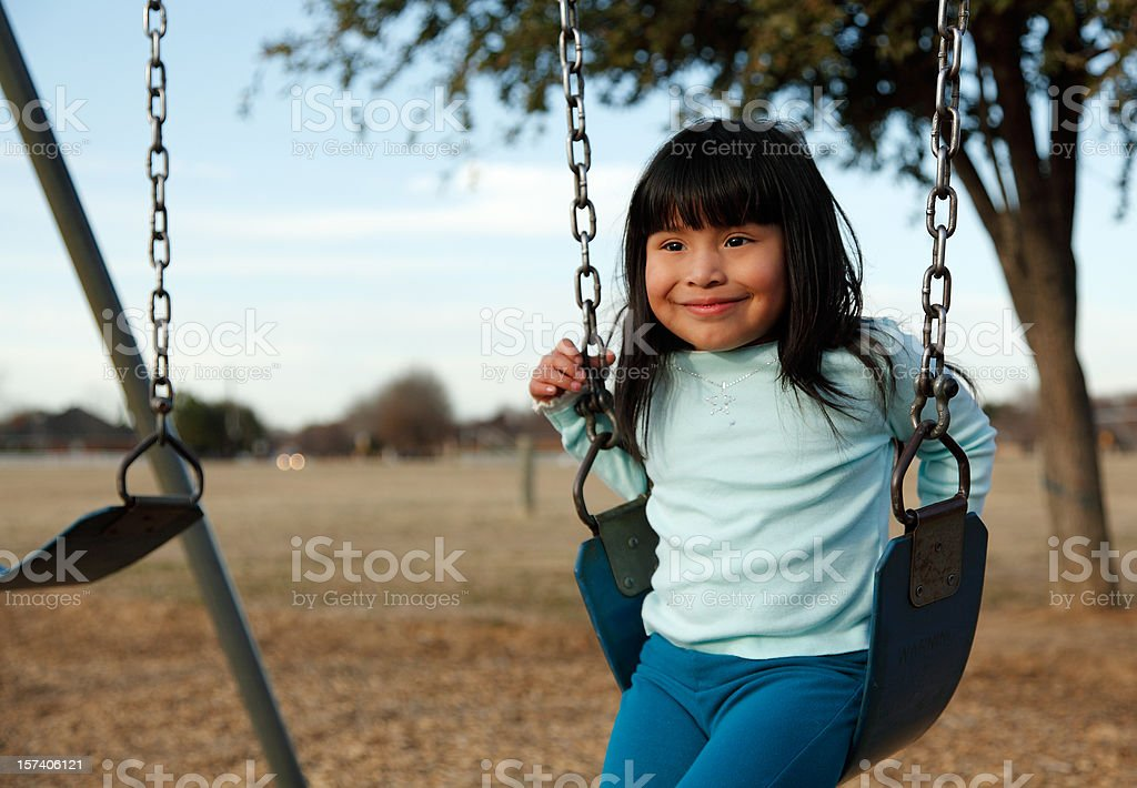 Little girl on a swingset stock photo