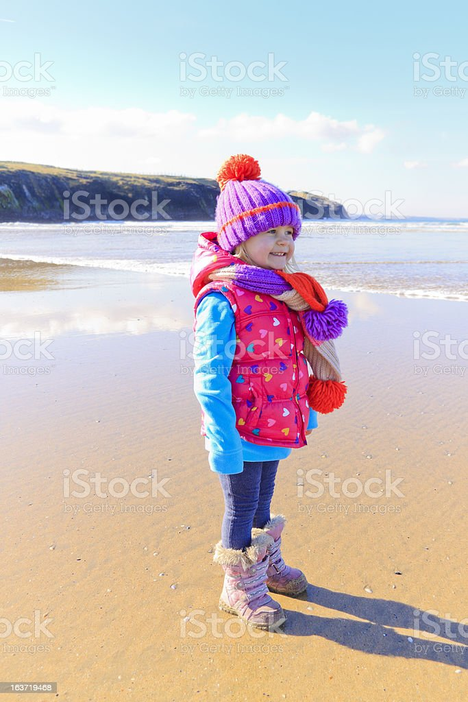 little girl on beach in winter clothing stock photo