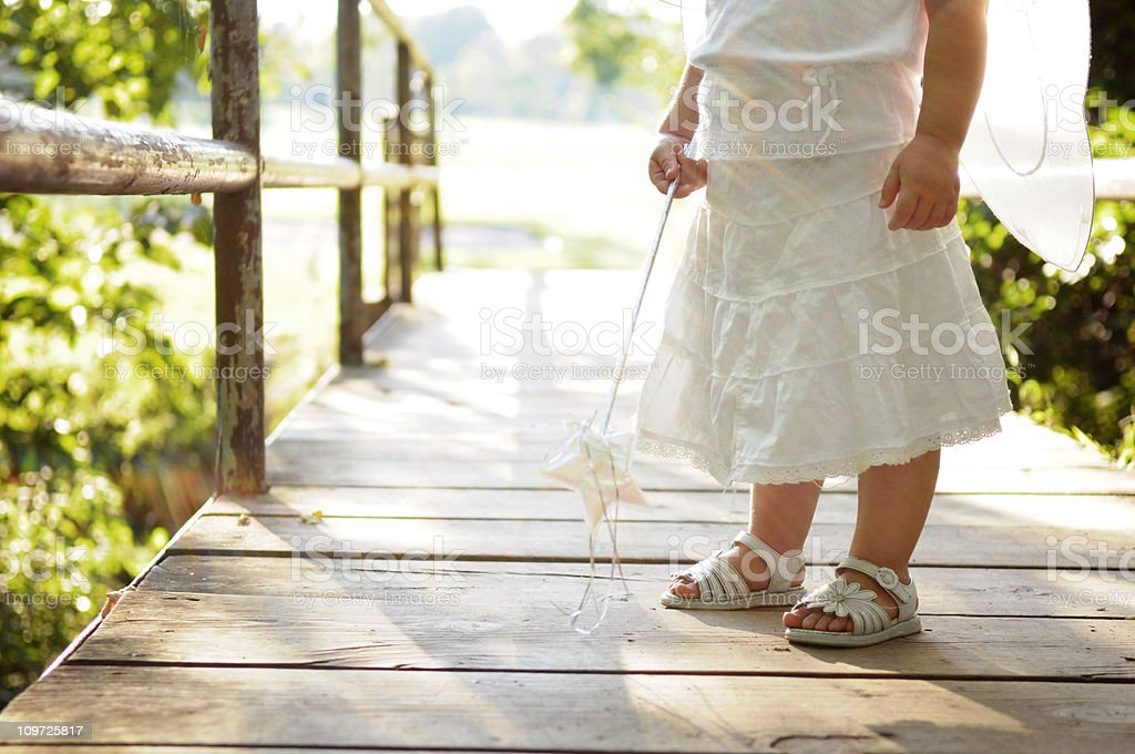 Petite fille portant sur le pont de fées et ailes tenant une douchette - Photo
