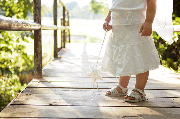 little girl on bridge wearing fairy wings and holding wand - fairy wand stock photos and pictures