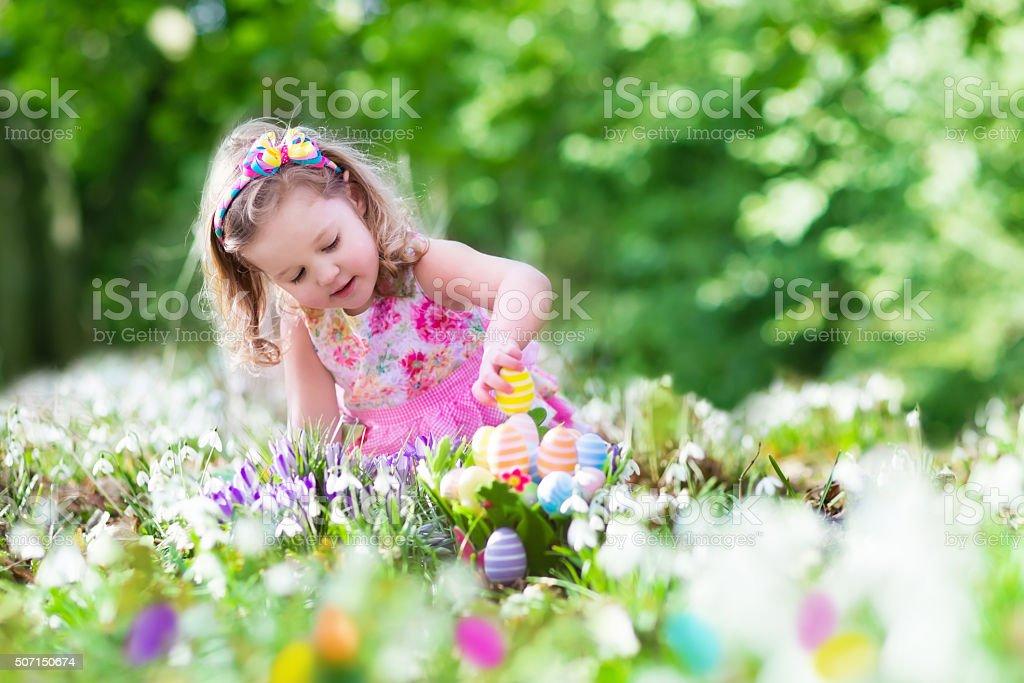 Little girl on Easter egg hunt stock photo