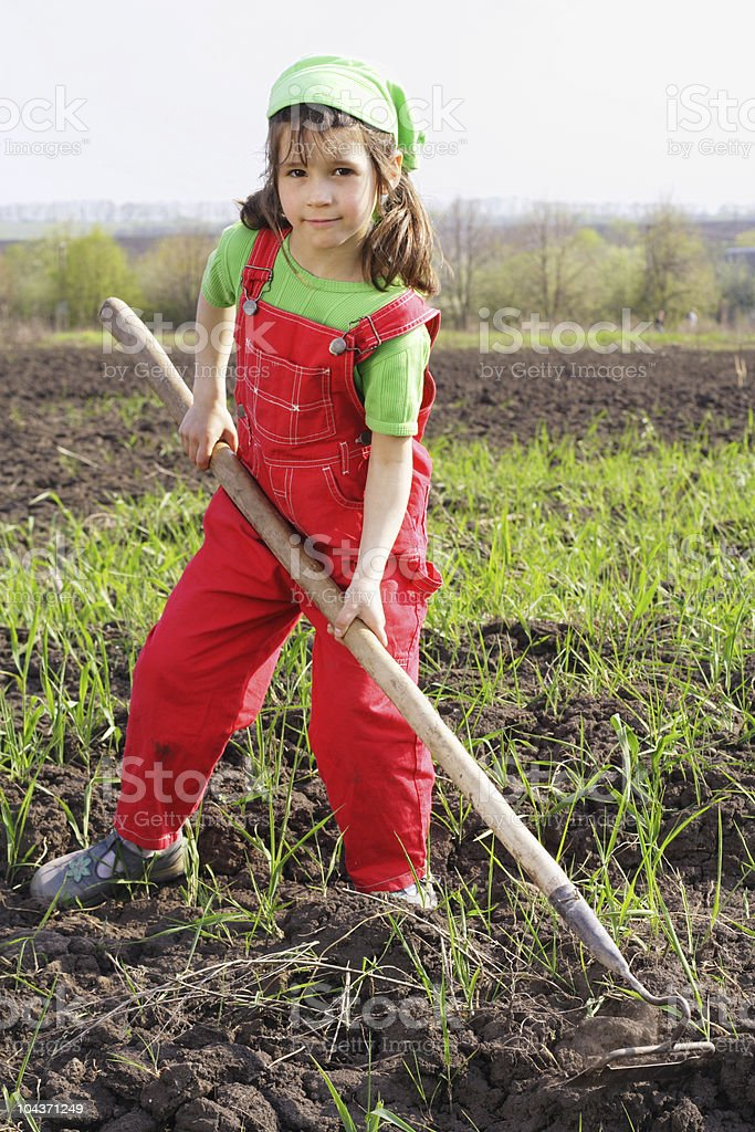 Little girl on field with hoe tool stock photo