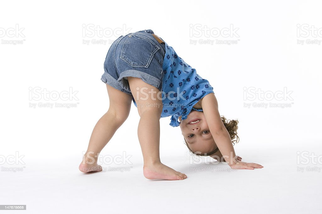 Little girl on hands and feet stock photo